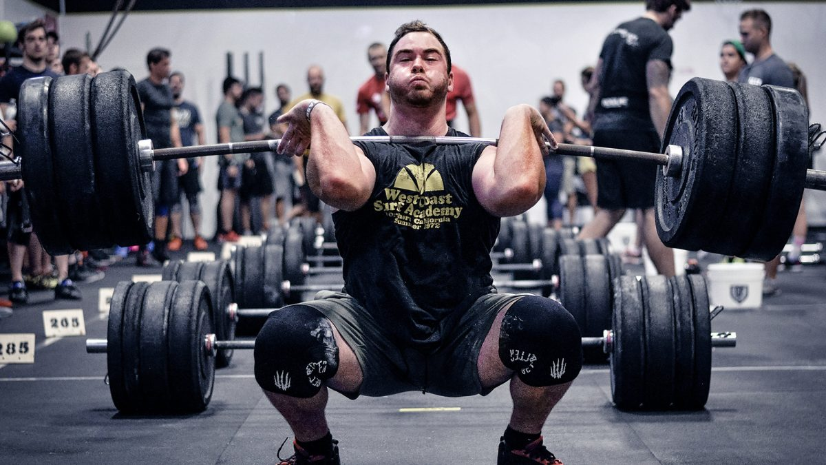 CrossFit athlete doing a heavy squat clean during a WOD workout