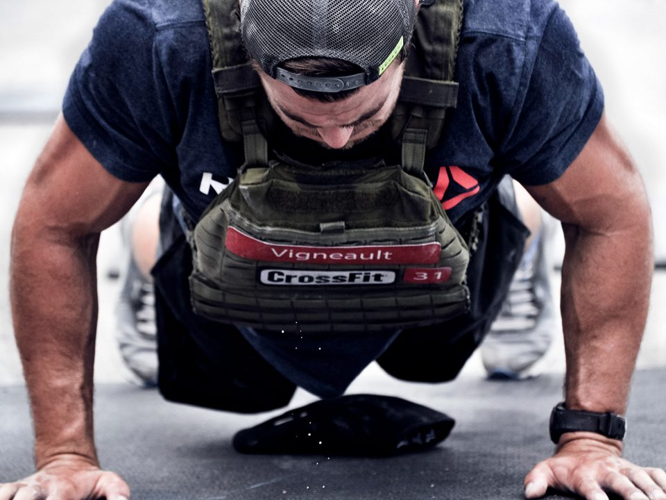 CrossFit games athlete Alex Vigneault dripping sweat doing a push up with a weighted vest during Murph WOD