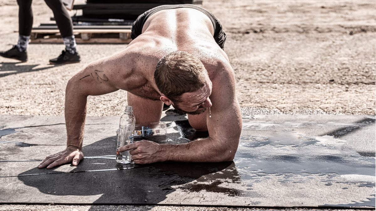 CrossFit athlete exhausted after WOD workout, dripping sweat in the floor