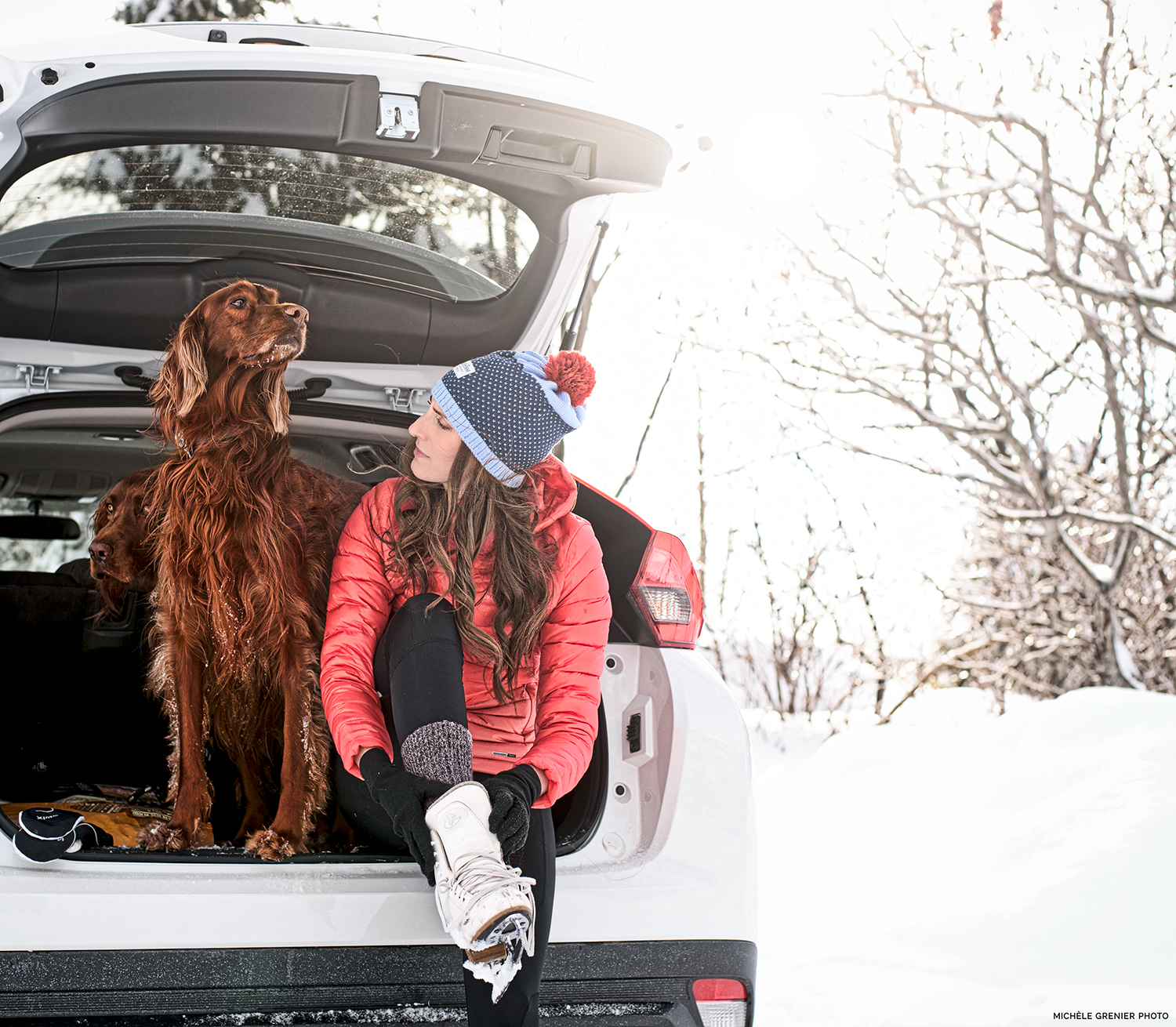 WOman and dog sit trunk car winter