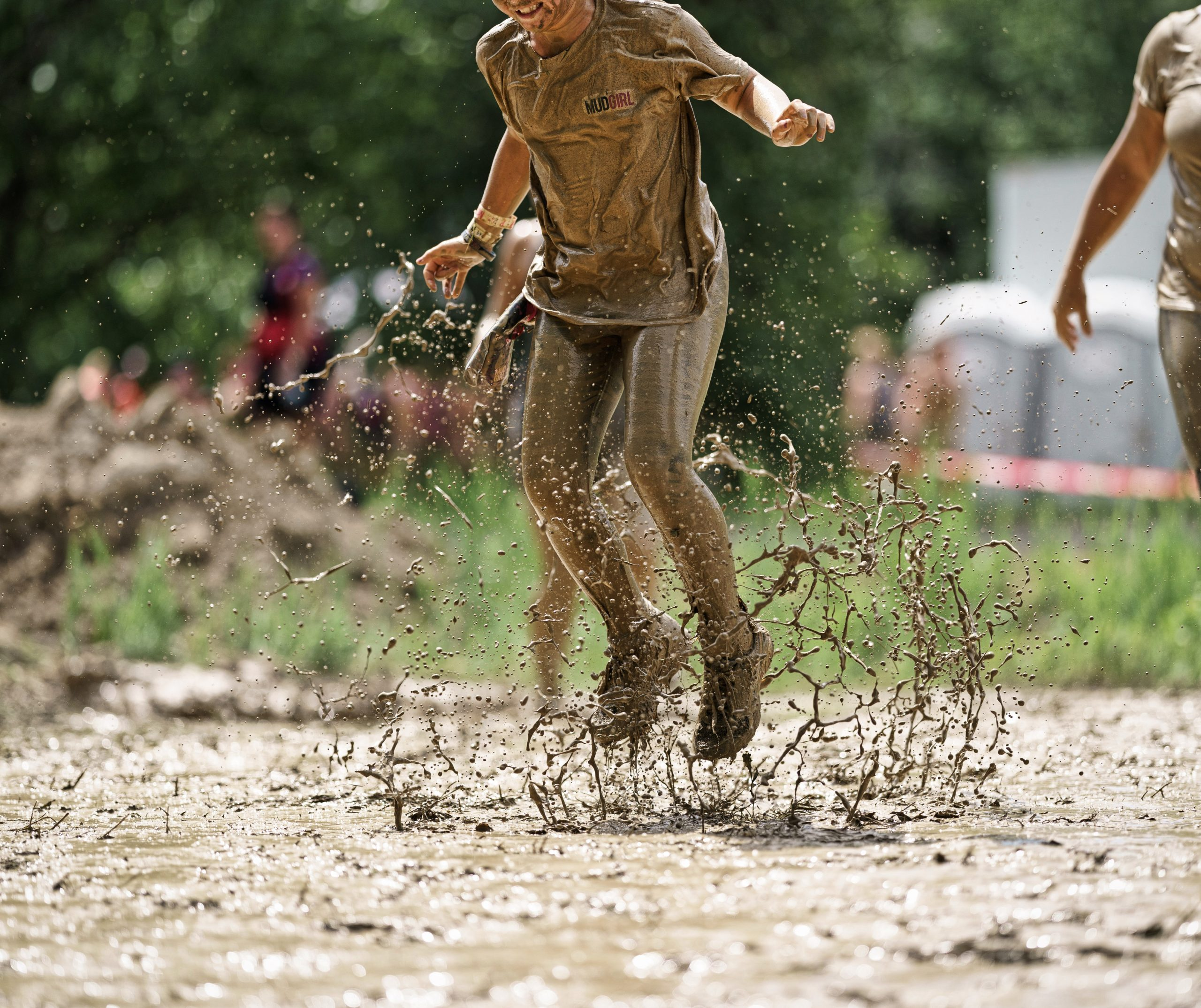 Girl jumping in mud
