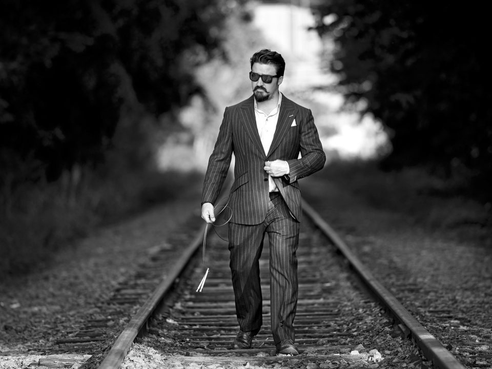 Black and white picture man walking on train rails