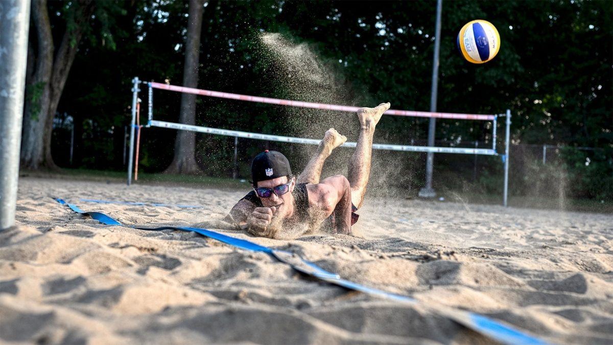 Beach volleyball athlete digging a ball in the sand
