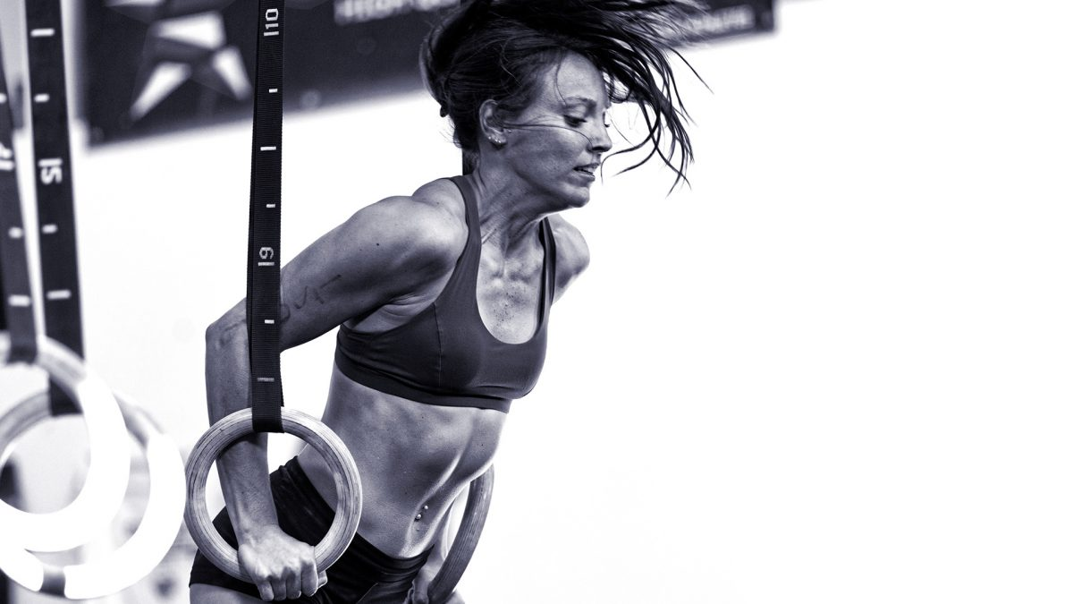 Female CrossFit athlete does a muscle up