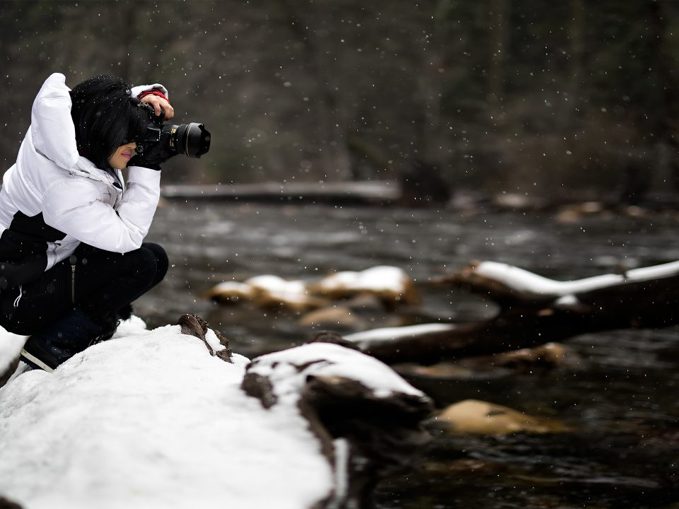 Female photographer takes pictures with camera by the river during winter