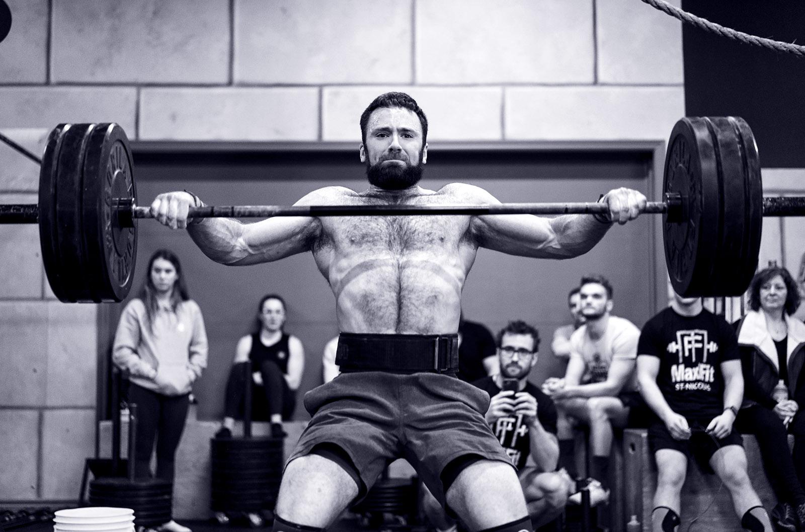 Athlète de CrossFit masculin qui fait un hang snatch à une compétition de sport