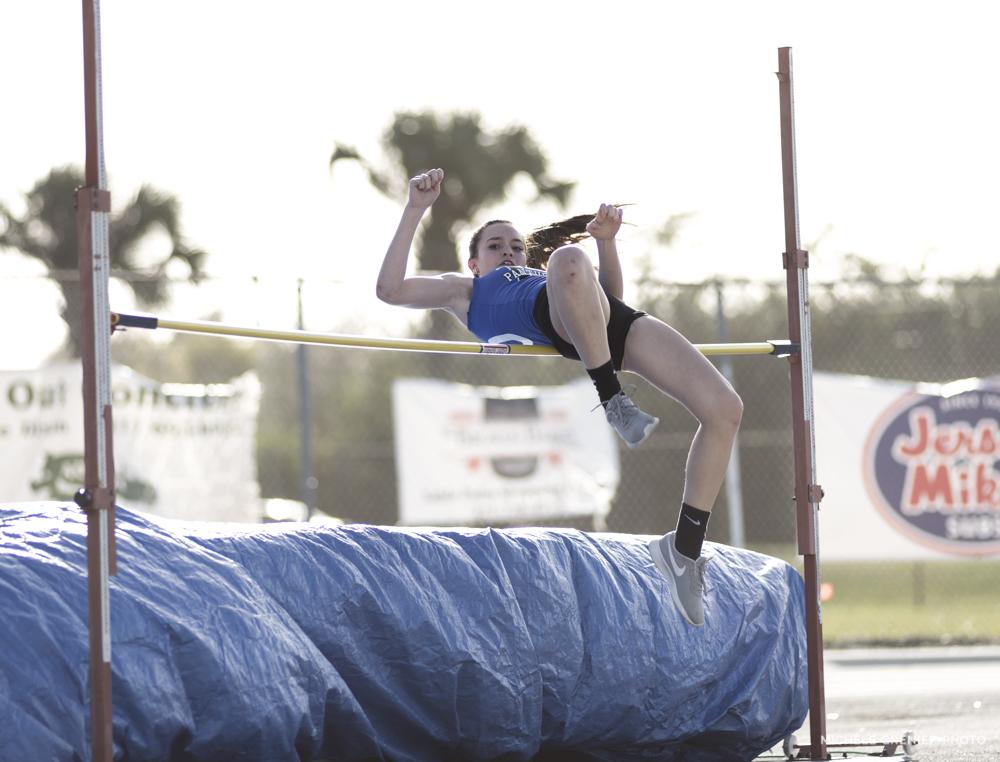 Athlète de sport féminine d'athlétisme qui fait réussi un saut en hauteur prise en photo