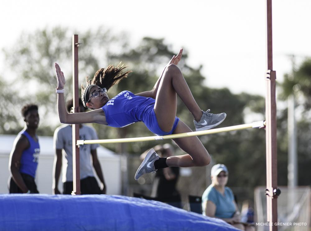 Athlète de sport féminine d'athlétisme qui fait réussit un saut en hauteur prise en photo
