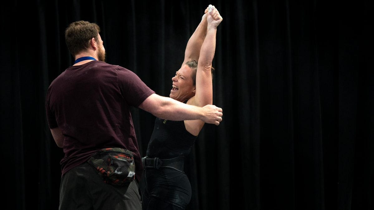 Female Weightlifter athlete celebrates successful lift sports event